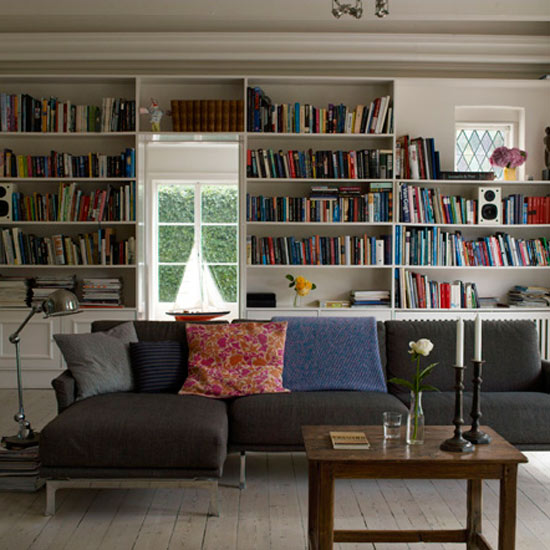 Modern-living-room-with-wooden-floor-modern-dark-sofa-bookshelves-simple-wooden-table-and-decorations
